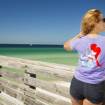 woman standing on pier wearing panama city beach mermaid shirt